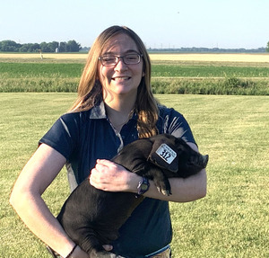 Grad student Katharine Sharpe holds a large black piglet
